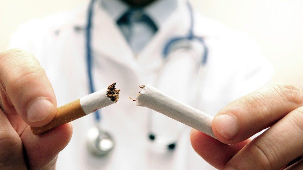 Médico contra tabagismo partindo um cigarro ao meio